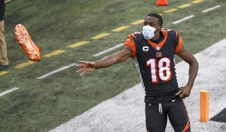 Cincinnati Bengals wide receiver A.J. Green (18) tosses a cleat to a fan after an NFL football game against the Baltimore Ravens, Sunday, Jan. 3, 2021, in Cincinnati. (AP Photo/Aaron Doster)