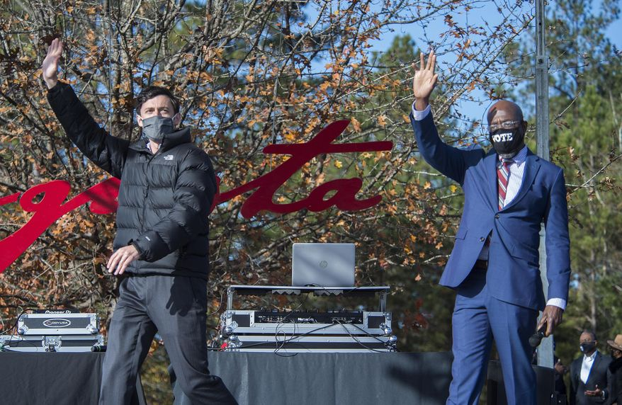 Jon Ossoff, left, and Raphael Warnock wave to the crowd during a campaign rally in Augusta, Ga., Monday, Jan. 4, 2021. Democrats Ossoff and Warnock are challenging incumbent Republican Senators David Perdue and Kelly Loeffler in a runoff election on Jan. 5. (Michael Holahan/The Augusta Chronicle via AP)