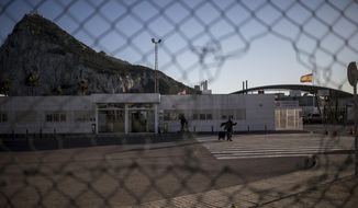 A woman walks at the border of Gibraltar with Spain, seen from the neighbouring Spanish city of La Linea on Thursday, Dec. 31, 2020. An 11th-hour breakthrough in protracted negotiations will keep open Gibraltar's border with Spain following the United Kingdom's full departure from the European Union. (AP Photo/Javier Fergo)