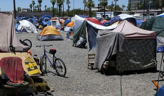 FILE - In this Wednesday, Aug. 5, 2020, file photo, a large homeless encampment is shown in Phoenix. Agencies that help the homeless in Arizona's largest county say the annual January count of people living on the streets has been canceled because of concerns about viral spread during the coronavirus pandemic.  (AP Photo/Ross D. Franklin, File)