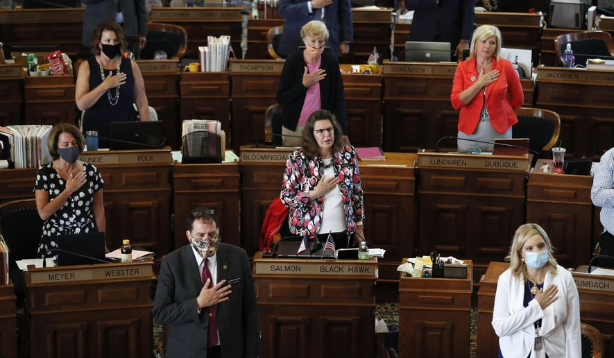 In this June 3, 2020, file photo, State Representatives stand at their desks during the Pledge of Allegiance in the Iowa House chambers, at the Statehouse in Des Moines, Iowa. As states brace for a coronavirus surge following holiday gatherings, one place stands out as a potential super-spreader site, the statehouses where lawmakers will help shape the response to the pandemic. (AP Photo/Charlie Neibergall, File)