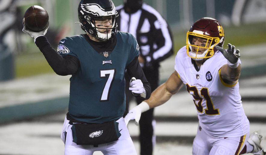 Philadelphia Eagles' Nate Sudfeld (7) passes against Washington Football Team's Ryan Kerrigan (91) during the second half of an NFL football game, Sunday, Jan. 3, 2021, in Philadelphia. (AP Photo/Derik Hamilton)