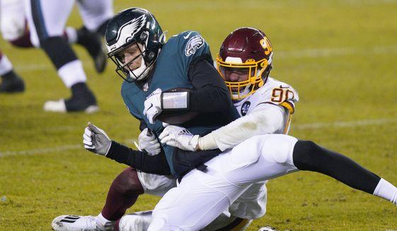 Philadelphia Eagles' Nate Sudfeld, left, is sacked by Washington Football Team's Montez Sweat during the second half of an NFL football game, Sunday, Jan. 3, 2021, in Philadelphia. (AP Photo/Chris Szagola) ** FILE **