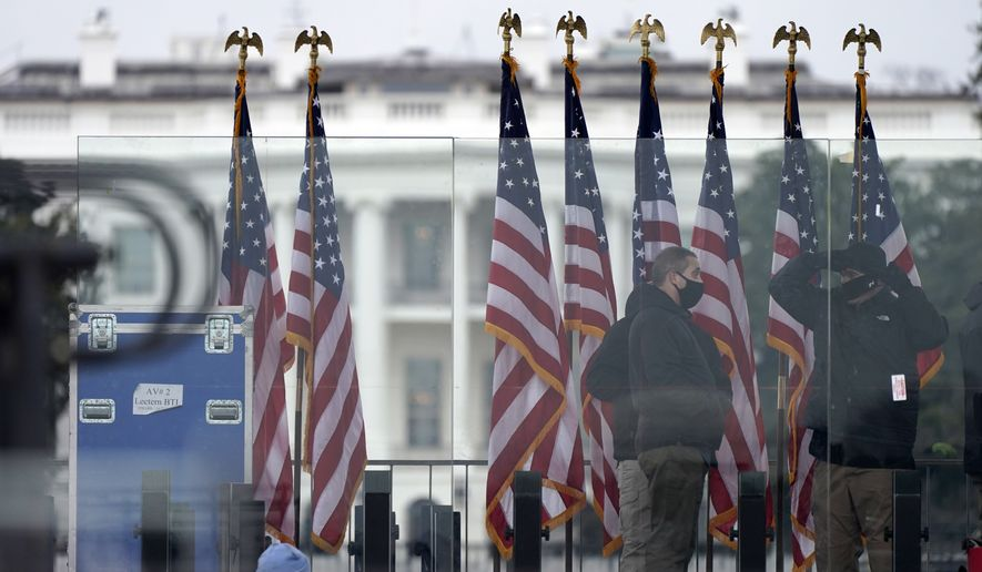 Workers build the stage on the ellipse near the White House on Tuesday, Jan. 5, 2021, ahead of expected rallies on Jan. 6 in support of President Donald Trump. (AP Photo/Jacquelyn Martin)