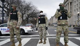 Members of the DC National Guard provide traffic control at an intersection near a rally at Freedom Plaza Tuesday, Jan. 5, 2021, in Washington, in support of President Donald Trump. (AP Photo/Jacquelyn Martin)