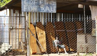 A worker at a coffin making company waits for clients inside the company premises in Harare, Tuesday, Jan. 5, 2021, as Zimbabwe began a 30-day lockdown in a bid to rein in the spike in COVID-19 infections threatening to overwhelm health services. In response to to rising infections the country has reintroduced a night curfew, banned public gatherings, and indefinitely suspended the opening of schools. (AP Photo/Tsvangirayi Mukwazhi)