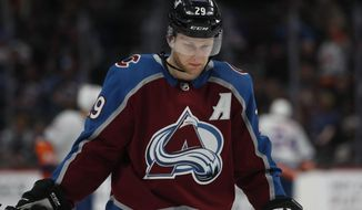 FILE - Colorado Avalanche center Nathan MacKinnon waits for a face off against the New York Islanders in the second period of an NHL hockey game in Denver, in this Wednesday, Feb. 19, 2020, file photo. MacKinnon views pressure almost like shots on goal — the more, the better. That's why the Colorado Avalanche forward fully embraces his team being mentioned among the Stanley Cup favorites. (AP Photo/David Zalubowski, File)