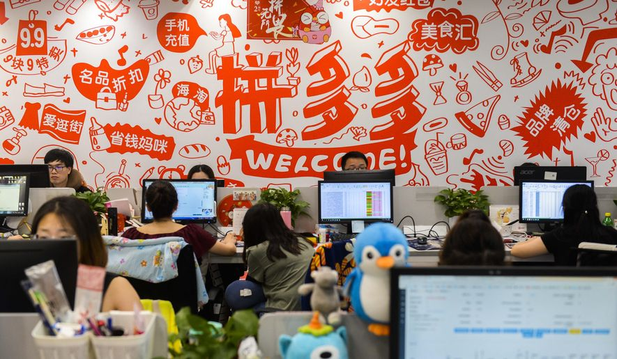 Workers sit on duty at the headquarters of Pinduoduo, an e-commerce platform, in Shanghai Wednesday, July 25, 2018. China's official Xinhua News Agency is calling for shorter work hours in the country's tech sector following the sudden death of a young employee at the leading e-commerce platform. (Chinatopix via AP)