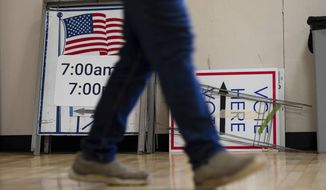 A worker passes voting signs while setting up a polling location at an elementary school in Gwinnett County, Ga., outside of Atlanta on Monday, Jan. 4, 2021, in advance of the Senate runoff election. (AP Photo/Ben Gray)