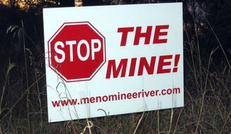 FILE - This Oct. 20, 2008 file photo shows, one of many signs that have popped up in yards, on trees and along roads in the Lake Township, Mich., section of Menominee County, where the proposed Aquila Resources Inc. mine would be located. Administrative Law Judge Daniel Pulter has overruled state regulators who granted a permit required for construction of the open-pit mine in the Upper Peninsula, in a decision released Monday. Jan. 4, 2021, creating another delay for a project that has been debated for nearly two decades.(AP Photo/John Flesher, File)