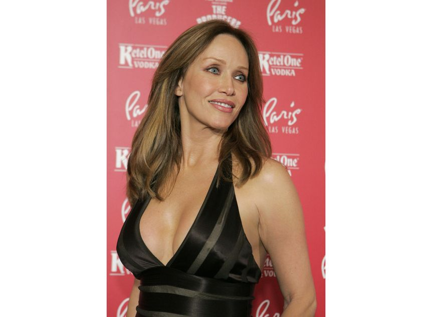 """Actress Tanya Roberts poses for photos at the grand opening of the musical comedy """"The Producers"""" at the Paris hotel-casino in Las Vegas on Feb. 9, 2007. Roberts, who captivated James Bond in """"A View to a Kill"""" and appeared in the sitcom """"That '70s Show,"""" died Monday,  Jan. 4, 2021, several hours after she was mistakenly declared dead by her publicist and her partner. Roberts' partner Lance O'Brien confirmed her death Tuesday after picking up her personal effects at a Los Angeles hospital. She was 65. (AP Photo/Jae C. Hong, File)"""