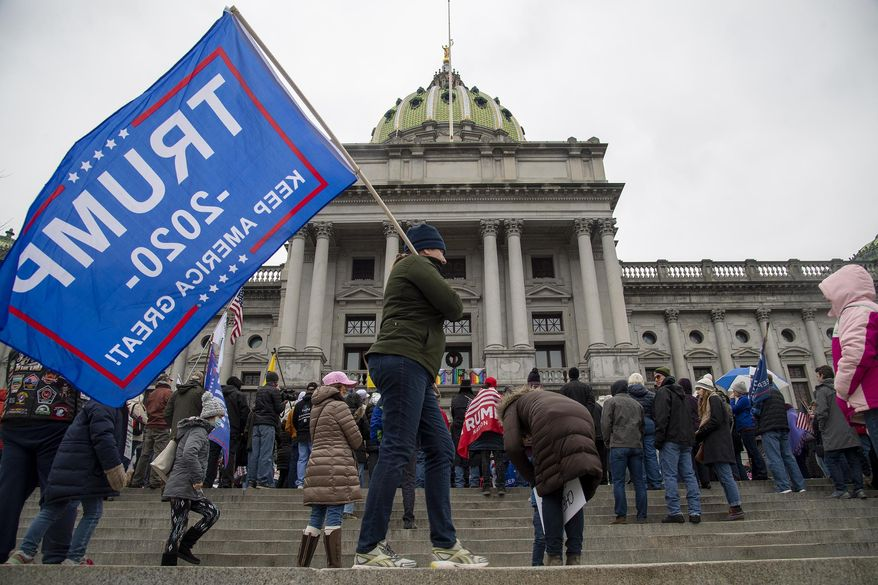 Trump supporters protest for Congress to de-certify election results during a rally on the steps of the Pennsylvania's State Capitol Building Harrisburg, Pa. Tuesday, Jan. 5, 2021. (Jose F. Moreno/The Philadelphia Inquirer via AP)