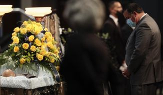 Columbus Mayor Andrew J. Ginther pays his respects at the casket of Andre Hill during funeral services on Tuesday, Jan. 5, 2021 at First Church of God in Columbus, Ohio.  Hill, a 47-year-old Black man, was shot and killed by Columbus Division of Police Officer Adam Coy in the early morning of Dec. 22, 2020 after officers responded to a non-emergency call in the area.  (Joshua A. Bickel/The Columbus Dispatch via AP)