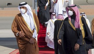 In this photo provided by the Saudi Royal Court, Saudi Arabia's Crown Prince Mohammed bin Salman, right, welcomes Qatar's Emir Sheikh Tamim bin Hamad al-Thani upon his arrival to attend the Gulf Cooperation Council's 41st Summit in Al-Ula, Saudi Arabia, Tuesday, Jan. 5, 2021. (Saudi Royal Court via AP)