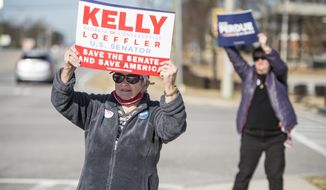 Jean Calvert, left, and Debbie Epling wave signs for their favorite candidates at the intersection Belair and Washington Roads during Georgia's U.S. Senate runoff election in Evans, Ga., Tuesday morning, Jan. 5, 2021. Republican Sen. Kelly Loeffler and David Perdue are being challenged by Democrats Jon Ossoff and Raphael Warnock in Tuesday's runoff. (Michael Holahan/The Augusta Chronicle via AP)