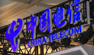 In this Sept. 5, 2020, file photo, the logo for Chinese telecommunications firm China Telecom is seen on a booth at the China International Fair for Trade in Services (CIFTIS) in Beijing.  (AP Photo/Mark Schiefelbein, File)  **FILE**