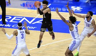 Vanderbilt's Scotty Pippen Jr., middle, looks for a teammate while defended by Kentucky's B.J. Boston (3), Olivier Sarr (30) and Davion Mintz (10) during the first half of an NCAA college basketball game in Lexington, Ky., Tuesday, Jan. 5, 2021. (AP Photo/James Crisp)