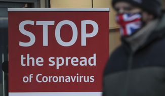 A man wearing a British union flag face mask walks past a coronavirus advice sign outside a bank in Glasgow the morning after stricter lockdown measures came into force for Scotland, Tuesday Jan. 5, 2021.  Further measures were put in place Tuesday as part of lockdown restrictions in a bid to halt the spread of the coronavirus.(Andrew Milligan/PA via AP)