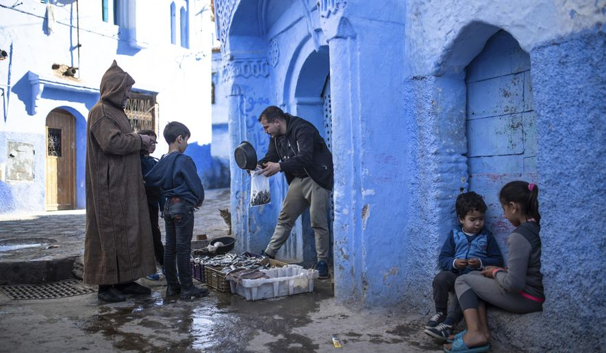 A fishermen sells his catch of the day in an alleyway in Chefchaouen, in northern Morocco, Saturday, Dec. 26, 2020. Known as the Blue Pearl of Morocco, the photogenic and mountainous town is usually overcrowded with tourists, but has been deserted this year due to the Covid-19 pandemic. (AP Photo/Mosa'ab Elshamy)