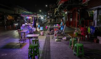 A lone street vender waits for customers at Khao San road, a once popular hangout with bars and entertainment for locals and tourists in Bangkok, Thailand, Monday, Jan. 4, 2021. Thailand on Tuesday, Jan. 5, 2021, reported over 500 new coronavirus cases, most of them migrant workers who already were isolated, and the government said it was tightening movements of people around the country. (AP Photo/Gemunu Amarasinghe)