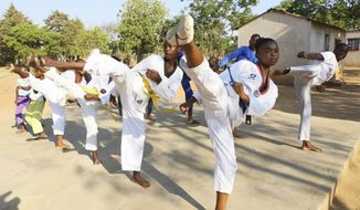 Natsiraishe Maritsa, second right, goes through taekwondo kicking drills during a practice session with young boys and girls in the Epworth settlement about 15 km southeast of the capital Harare, Saturday Nov. 7, 2020. In Zimbabwe, where girls as young as 10 are forced to marry due to poverty or traditional and religious practices, a teenage martial arts fan 17-year old Natsiraishe Maritsa is using the sport to give girls in an impoverished community a fighting chance at life. (AP Photo/Tsvangirayi Mukwazhi)