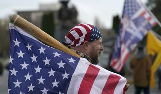A man carries a U.S. flag attached to a baseball bat as he waits at the Capitol in Olympia, Wash., Wednesday, Jan. 6, 2021, before the start of a protest rally against the counting of electoral votes in Washington, DC, affirming President-elect Joe Biden's victory. People supporting President Donald Trump and other supporters began arriving at the Capitol mid-morning for a protest rally Wednesday that was expected to begin at noon. (AP Photo/Ted S. Warren)
