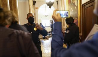 U.S. Capitol Police hold protesters on the floor at gun-point as protesters try to break into the House Chamber at the U.S. Capitol on Wednesday, Jan. 6, 2021, in Washington. (AP Photo/Andrew Harnik)