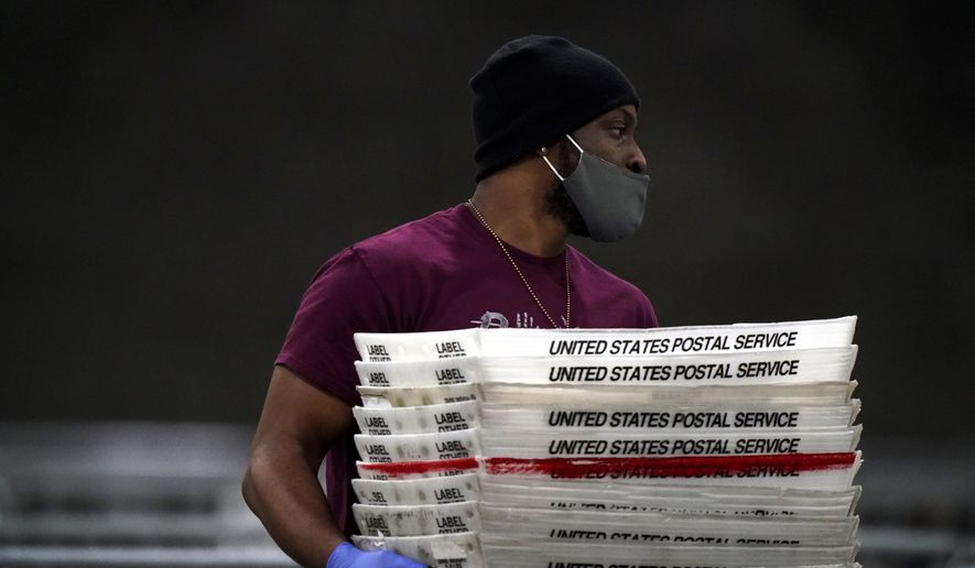 An official moves stacks of U.S. postal service trays as ballots are counted for Georgia's Senate runoff election at the Georgia World Congress Center on Wednesday, Jan. 6, 2021, in Atlanta. (AP Photo/Brynn Anderson)