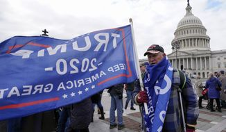 Supporters of President Donald Trump cary flags and banners on Capitol Hill during a rally, Wednesday, Jan. 6, 2021. in Washington. (AP Photo/Manuel Balce Ceneta)