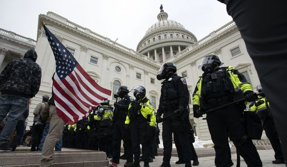 U.S. Capitol Police officers push back demonstrators who were trying to break into the U.S. Capitol on Wednesday, Jan. 6, 2021, in Washington. (AP Photo/Jose Luis Magana)