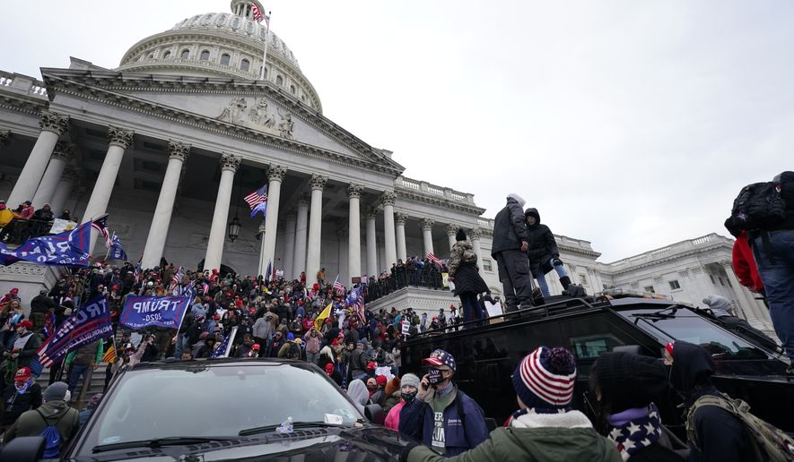 Trump supporters stand on top of a police vehicle, Wednesday, Jan. 6, 2021, at the Capitol in Washington. As Congress prepares to affirm President-elect Joe Biden's victory, thousands of people have gathered to show their support for President Donald Trump and his claims of election fraud. (AP Photo/Julio Cortez)