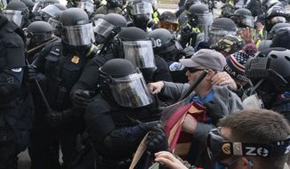 Capitol police officers in riot gear push back demonstrators who try to break a door of the U.S. Capitol on Wednesday, Jan. 6, 2021, in Washington. (AP Photo/Jose Luis Magana) **FILE**