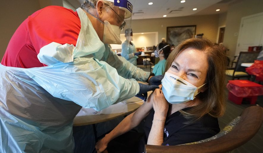 Health care worker Pam Peter, right, prepares to receive her second round of the COVID-19 vaccine, Wednesday, Jan. 6, 2021, at John Knox Village in Pompano Beach, Fla. Ninety residents and 80 staff members received their second shot of the vaccine Wednesday and 50 new staff members received their first round of the vaccine. (AP Photo/Wilfredo Lee)