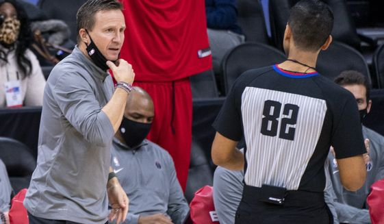 Washington Wizards head coach Scott Brooks, left, reacts to referee Suyash Mehta, right, during the second half of an NBA basketball game against the Philadelphia 76ers, Wednesday, Jan. 6, 2021, in Philadelphia. The 76ers won 141-136. (AP Photo/Chris Szagola)