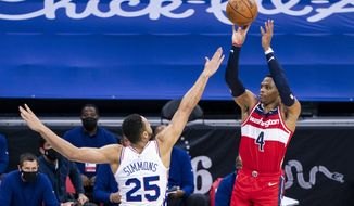 Washington Wizards guard Russell Westbrook, left, shoots the ball against Philadelphia 76ers guard Ben Simmons, right, during the second half of an NBA basketball game, Wednesday, Jan. 6, 2021, in Philadelphia. The 76ers won 141-136. (AP Photo/Chris Szagola)