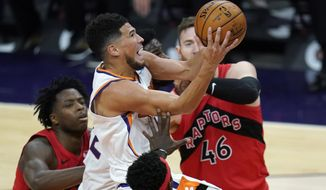Phoenix Suns guard Devin Booker, middle, drives past Toronto Raptors center Aron Baynes (46) and Raptors forward OG Anunoby, left, during the second half of an NBA basketball game Wednesday, Jan. 6, 2021, in Phoenix. (AP Photo/Ross D. Franklin)