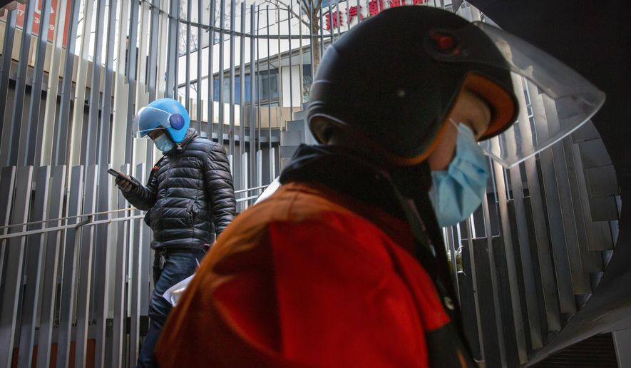 Delivery drivers wearing face masks to protect against the coronavirus walk along a staircase at an office and shopping complex in Beijing, Wednesday, Jan. 6, 2021. China's Hebei province is enforcing stricter control measures following a further rise in coronavirus cases in the province, which is adjacent to the capital Beijing and is due to host events for next year's Winter Olympics. (AP Photo/Mark Schiefelbein)