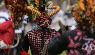 People dressed as devils dance in La Diablada Pillarena amid the COVID-19 pandemic in Pillaro, Ecuador, Wednesday, Jan. 6, 2021. Performers took to the streets of this small city in the center of the country with only 40 characters dancing in a closed place and without an audience. (AP Photo/Dolores Ochoa)