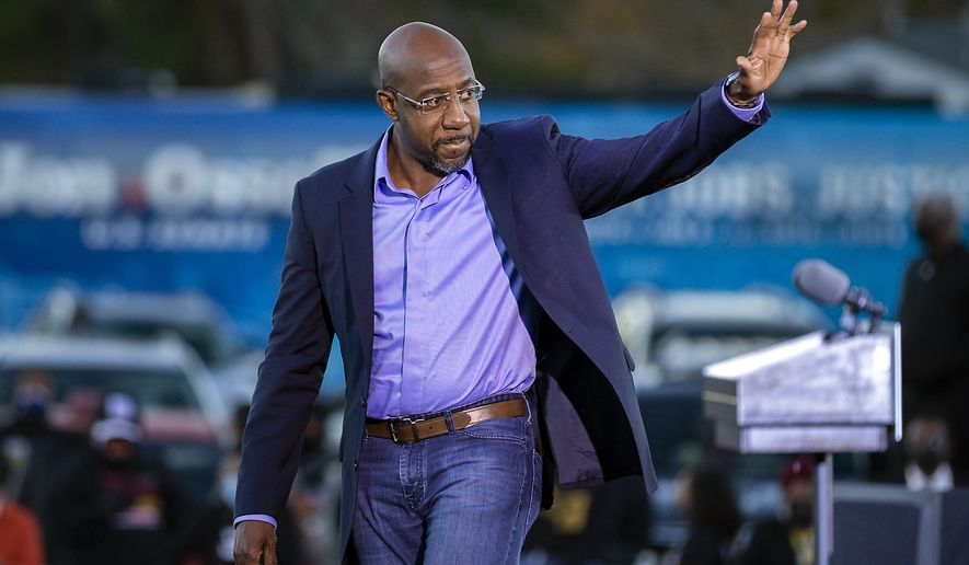 Democratic U.S. Senate candidate Rev. Raphael Warnock waves to supporters during a drive-in rally, Sunday, Jan. 3, 2021, in Savannah, Ga. Vice President-elect Kamala Harris made a campaign stop for Georgia candidates Warnock and Jon Ossoff before the runoff election Tuesday. (AP Photo/Stephen B. Morton)