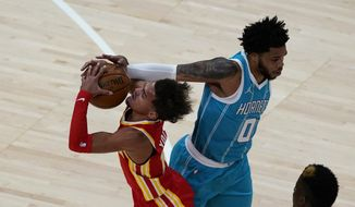 Atlanta Hawks guard Trae Young, left, tries to drive past Charlotte Hornets forward Miles Bridges (0) during the first half of an NBA basketball game Wednesday, Jan. 6, 2021, in Atlanta. (AP Photo/John Bazemore)