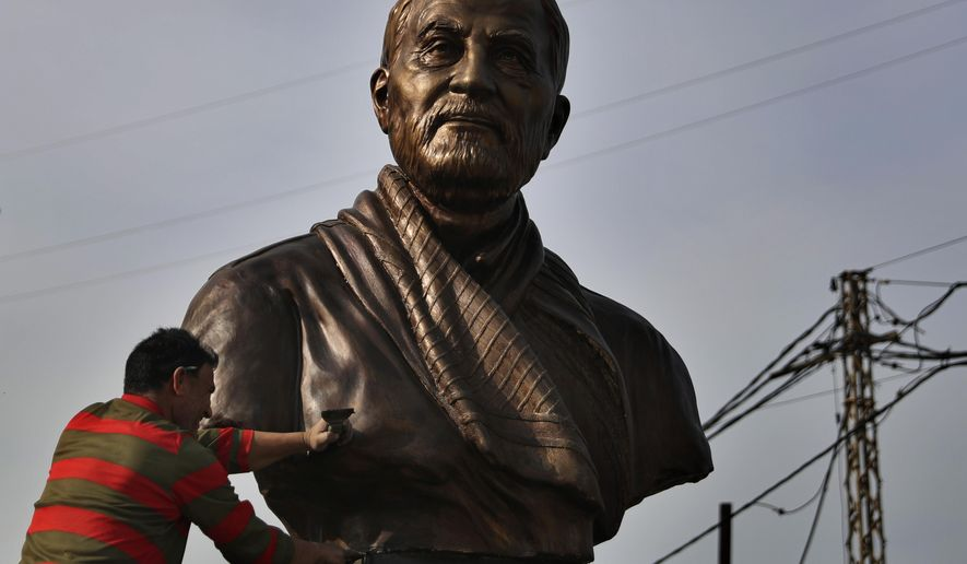 A worker cleans a statue of Iranian General Qassem Soleimani, installed to commemorate the anniversary of  his killing, in a U.S. drone strike in Baghdad, in Ghobeiry, a southern suburb of Beirut, Lebanon, Wednesday, Jan. 6, 2021. (AP Photo/Bilal Hussein)