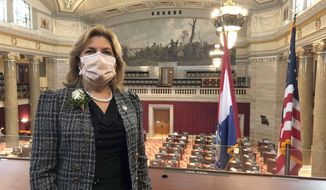 Missouri state Rep. Brenda Shields stands in a gallery overlooking the Missouri House chamber on the opening day of the legislative session, Wednesday, Jan. 6, 2021, in Jefferson City, Missouri. Shields said she tested positive for COVID-19 in November, around the time the House last meet in session. She is encouraging colleagues to wear masks and take precautions. (AP Photo/David A. Lieb)