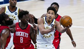 Indiana Pacers guard Malcolm Brogdon (7) shoots in front of Houston Rockets forward Jae'Sean Tate (8) during the first quarter of an NBA basketball game in Indianapolis, Wednesday, Jan. 6, 2021. (AP Photo/Michael Conroy)