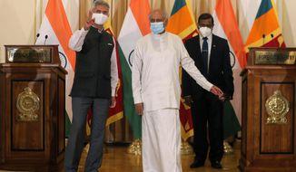 Sri Lankan Foreign Minister Dinesh Gunawardena stands for a photograph with his Indian counterpart Subrahmanyam Jaishankar, left, after addressing a joint media briefing in Colombo, Sri Lanka, Wednesday, Jan. 6, 2021. (AP Photo/Eranga Jayawardena)
