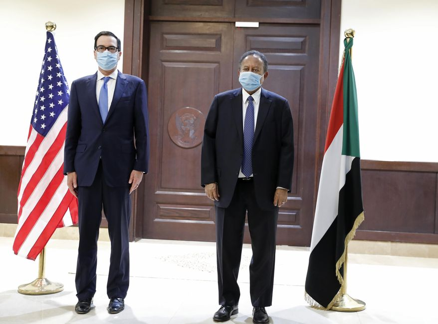 Sudanese Prime Minister Abdullah Hamdok, right, welcomes US Treasury Secretary Steven Mnuchin to the Cabinet Building, in Khartoum, Sudan, Wednesday, Jan. 6, 2021. The U.S. and Sudan have agreed to settle the African country's debt to the World Bank. The move comes after Mnuchin arrived in Sudan, the first visit by a senior American official since President Donald trump removed Sudan from the list of state sponsors of terrorism. (AP Photo)