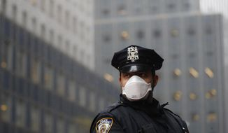 FILE - In this, May 1, 2020, file photo, a New York Police officer wears a mask to protect against coronavirus during a May Day protest outside the offices of New York Gov. Andrew Cuomo in New York. New York City Mayor Bill de Blasio and Gov. Andrew Cuomo are again at odds, this time over city police officers' eligibility for COVID-19 vaccines. (AP Photo/John Minchillo, File)