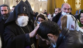 Armenian Catholicos Karekin II wearing a face mask to protect against coronavirus, left, blesses a believer after the Christmas Mass in the Saint Gregory the Illuminator Cathedral in Yerevan, Armenia, Wednesday, Jan. 6, 2021. Armenia's prime minister, who is under harsh criticism from the country's dominant Orthodox Christian church in connection with the recent war with Azerbaijan, stayed away from Christmas services on Wednesday. Orthodox Christians celebrate Christmas on Jan. 7, in accordance with the Julian calendar. (Grigor Yepremyan/PAN Photo via AP)