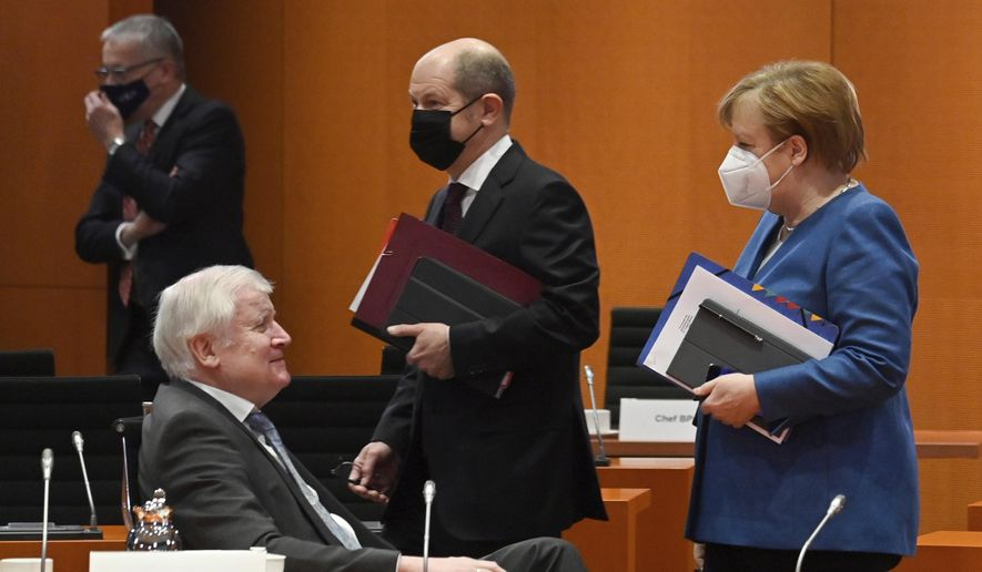 German Chancellor Angela Merkel walks beside Federal Finance Minister Olaf Scholz and Interior Minister Horst Seehofer, from right, prior the weekly cabinet meeting on Wednesday, Jan. 6, 2021 at the Chancellery in Berlin, Germany. (John MacDougall/Pool via AP)