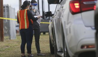 Staff help register and process those waiting in their vehicles in the line for non-ambulatory people to be vaccinated Tuesday, Jan. 5, 2021, at the COVID-19 vaccination clinic on the Rio Grande Valley Livestock Show grounds in Mercedes, Texas. (Denise Cathey/The Brownsville Herald via AP) **FILE**