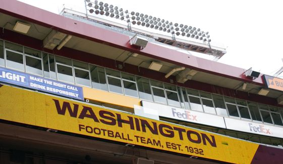 Fedex Field scoreboard displays the Washington Football Team name during warmups before the start of a NFL football game between Washington Football Team and Philadelphia Eagles, Sunday, Sept. 13, 2020, in Landover, Md. Washington has dumped its 86-year-old team name, handed over an investigation into workplace misconduct to the NFL, seen minority owners and Dan Snyder battle it out in court, coach Ron Rivera battle a form of skin cancer and reached the playoffs on the arm of a quarterback who hadn't played in two years because of an injury that looked career-threatening. All in a few months' work for arguably the biggest soap opera in professional sports with a playoff game against Tom Brady up next. (AP Photo/Susan Walsh) **FILE**